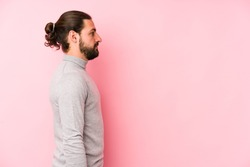 Young long hair man isolated on a pink background gazing left, sideways pose.