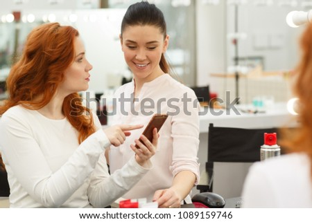 Young long haired beautiful woman talking to her hairdresser showing her haircut she wants on the smart phone. Professional hairstylist discussing haircuts with her female customer