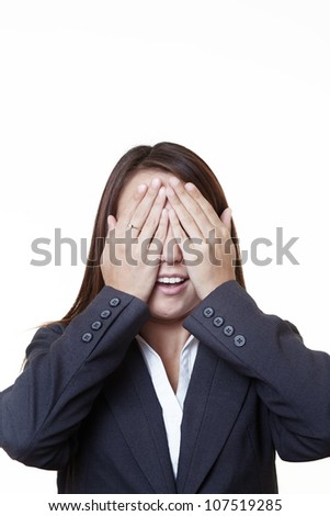 young looking woman in a suit covering her eyes with her hands