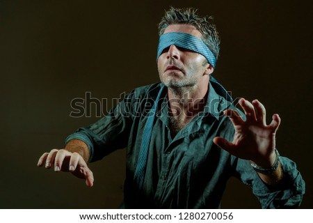 9dab693776a young lost and confused man blindfolded with necktie playing internet trend  dangerous viral challenge with eyes