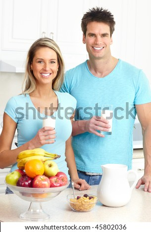 Young love couple  drinking milk at kitchen - stock photo