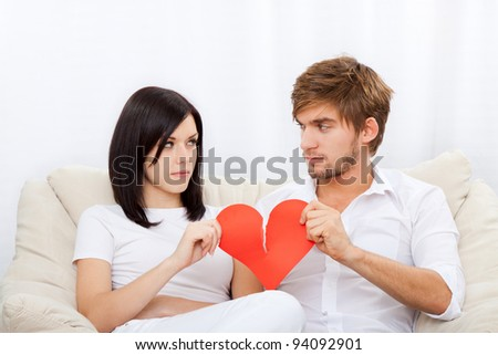 young love couple holding and break red valentine's heart together sitting on couch at home, unhappy looking to each other, valentine day no love concept