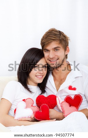 young love couple holding lot of red valentine's heart together sitting on couch at home, excited happy smile looking at camera, hug, valentine day love concept