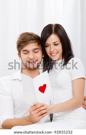 young love couple holding reading valentine's greeting card, note, letter with red heart, happy smile, hug, sitting on couch, valentine day concept