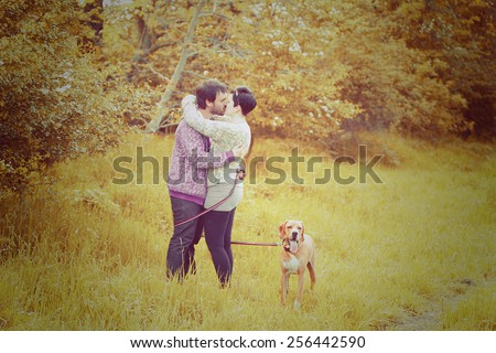 young love couple man and woman kiss on walk with dog in autumn nature