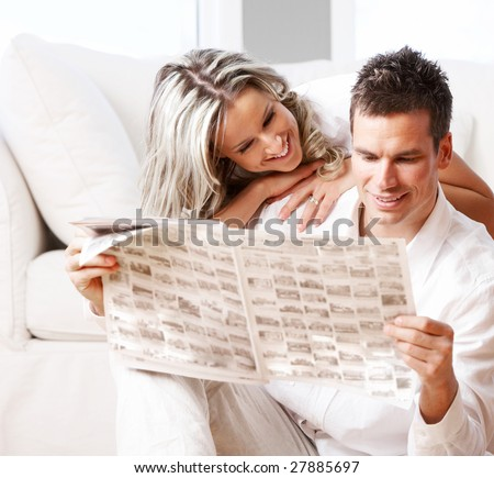 Young love couple reading magazine  in the comfortable apartment