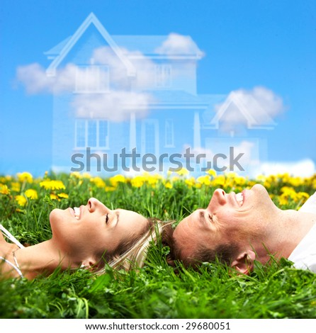 Young love couple smiling dreaming about a new home.  Real estate concept