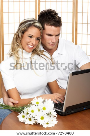 Young love couple with laptop. Over white background