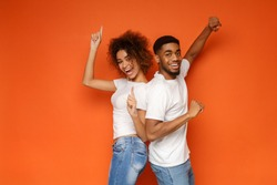 Young lovely african-american couple standing together and laughing, posing on orange background, copy space