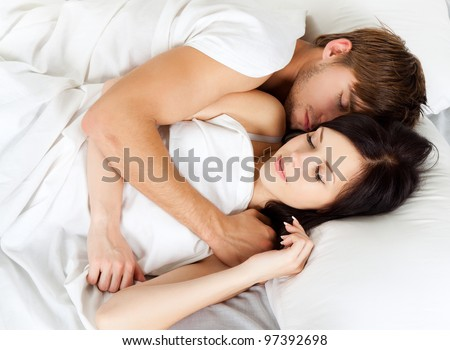 young lovely beautiful couple lying sleeping in a bed, closed eyes