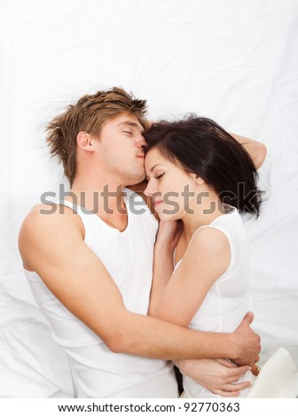 young lovely beautiful couple lying sleeping in a bed, top view.