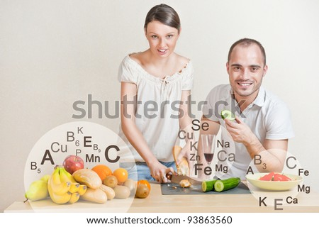 Young lovely couple cooking a balanced diet. Big copyspace. Vitamins and microelements symbols are around them. - stock photo