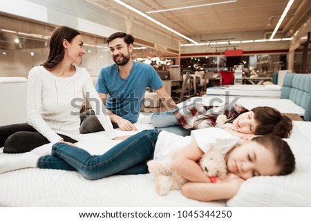 Young lovely couple is sitting on mattress next to sleeping children in furniture store. Testing softness of mattress. Choosing mattress in store