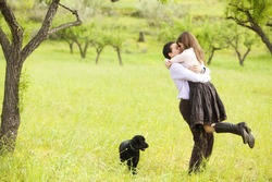 Young lovely couple kissing under nature.