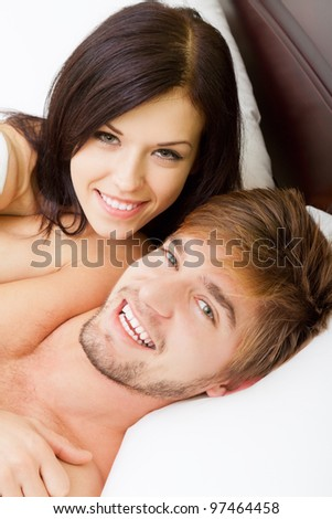 young lovely couple lying in a bed, happy smile looking at camera, close up view