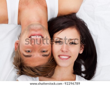 young lovely couple lying in a bed, happy smile looking at camera, top view.