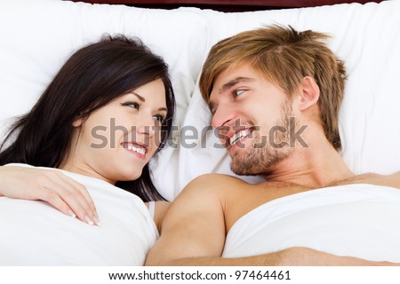 young lovely couple lying in a bed, happy smile looking to each other, top view