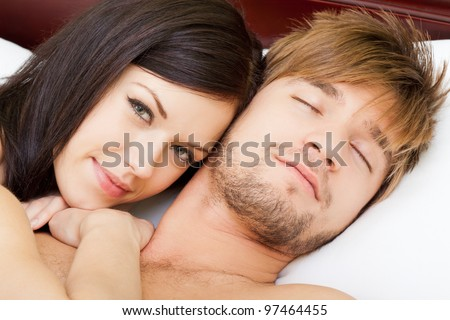 young lovely couple lying in a bed, happy smile woman looking at camera, man sleep with closed eyes, close up view.