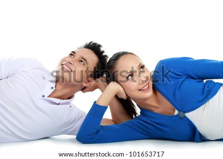 young lovely couple lying on the floor looking up to the copy space