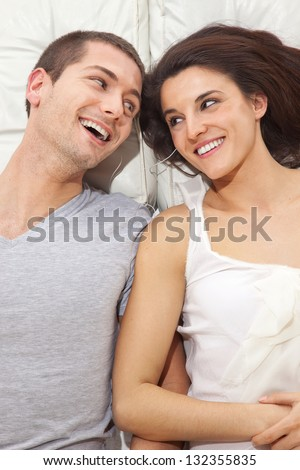 Young lovely couple together lying in a bed and listening music   / A smiling couple lying with headphones