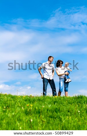 Young lovely family standing on a spring hill