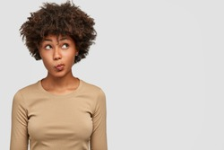 Young lovely female has dark skin, clueless and unaware expression, purses lips as being questionned, looks with puzzlement upwards, isolated over white background with copy space on right side