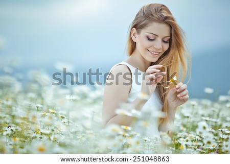 Young lovely smiling woman wonders on flower, tearing petals, close-up.
