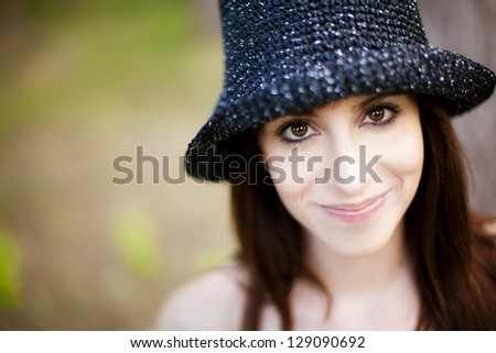 Young lovely woman portrait wearing hat under natural light.
