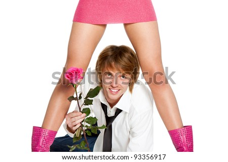 young lover man happy smile hold pink rose flower, lying under between woman sexy legs in skirt, concept of couple valentine's, greeting, valentine day love