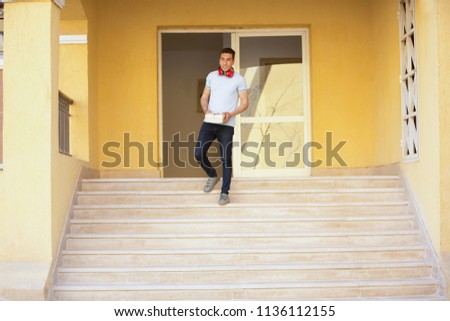 Young lover puts headphone around neck holds a gift descent the stairs to meet his friend.
