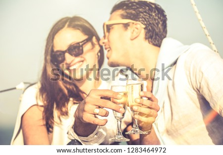 Young lovers couple on sailboat with focus on champagne flute glass cheer - Happy exclusive alternative lifestyle concept - Boyfriend whispering girlfriend ear on luxury sailboat - Warm vintage filter