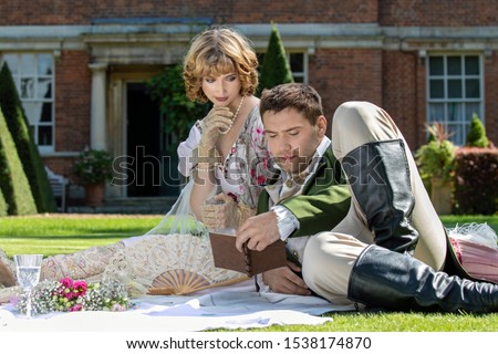 Young lovers dressed in vintage clothing sitting on picnic blanket. Gentleman is reading to his lover from a book of poems #1538174870