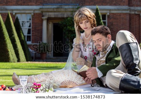 Young lovers dressed in vintage clothing sitting on picnic blanket. Gentleman is reading to his lover from a book of poems #1538174873