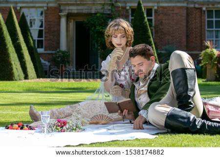 Young lovers dressed in vintage clothing sitting on picnic blanket. Gentleman is reading to his lover from a book of poems #1538174882