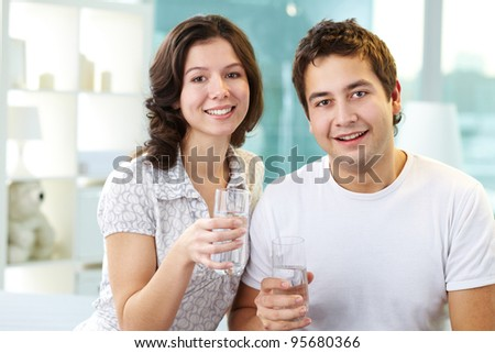Young lovers holding glasses of water and looking at camera