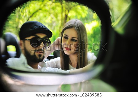 Young lovers in a side mirror of a car
