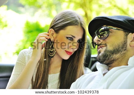 Young lovers in a sports car outdoors