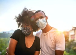 Young lovers of African ethnicity wearing the protective mask at sunset.