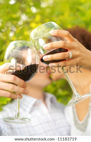 Young lovers on a romantic picnic outside, drinking wine and kissing - stock photo