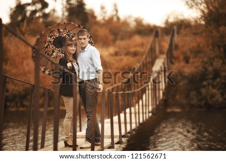 young lovers on a rope bridge across the river under the umbrella