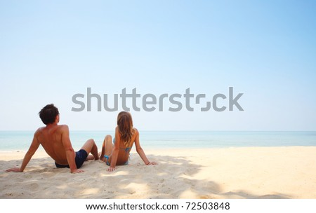 Young lovers sitting on sand and looking to a clear blue sky