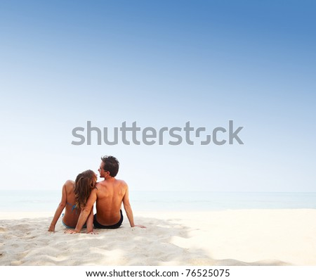 Young lovers sitting on warm beach at sunny day and enjoying each other