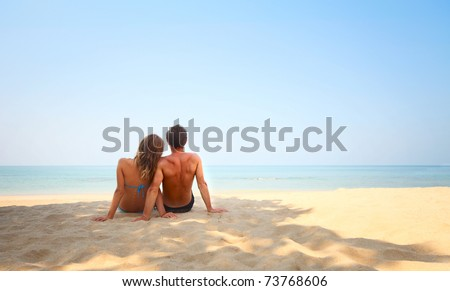 Young lovers sitting on warm sand at sunny day and looking to a clear blue sky