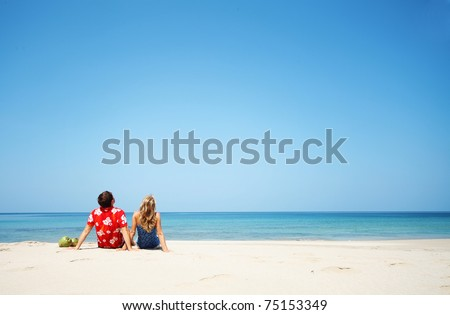 Young lovers sitting on warm sand at sunny day and looking to somewhere