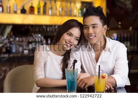 Young lovers spending an evening in a bar or a cafe over cocktails