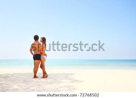 Young lovers standing on warm sand at sunny day and enjoying each other