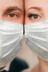 Young loving brides walking in modern city medical masks during quarantine on their wedding day. Coronavirus, disease, protection, sick, illness flu europe celebration canceled, surgical protective