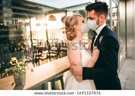 Young loving brides walking in modern city medical masks during quarantine on their wedding day. Coronavirus, disease, protection, sick, illness flu europe celebration canceled, surgical protective