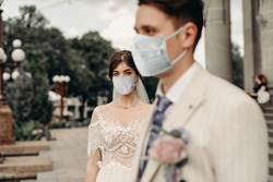 Young loving brides walking in the city in medical masks during quarantine on their wedding day. Coronavirus, disease, protection, sick, illness
