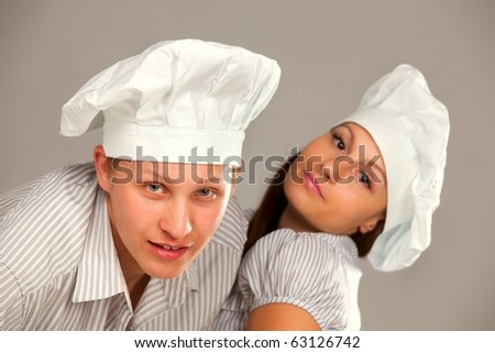 Young loving couple cooks. Over gray background